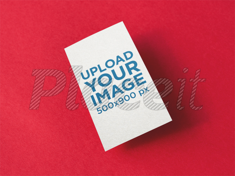 vertical business card mockup floating over a red surface a14991foreground image