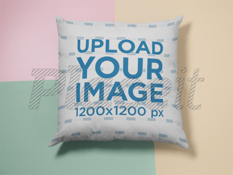 placeit square pillow template lying on a surface with three colors